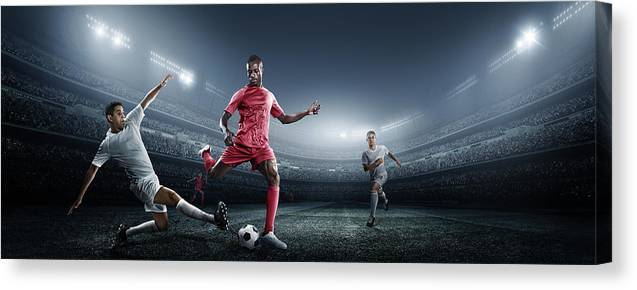 Soccer Uniform Canvas Print featuring the photograph Soccer Player Kicking Ball In Stadium by Dmytro Aksonov