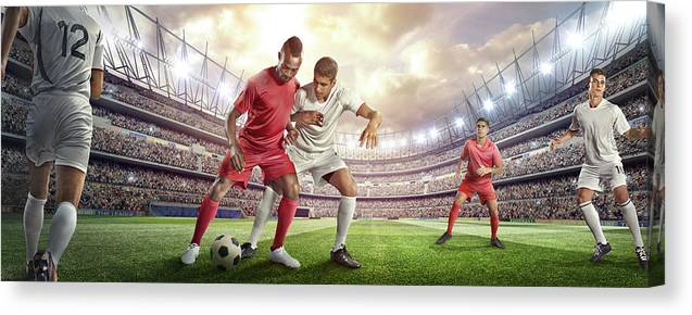 Soccer Uniform Canvas Print featuring the photograph Soccer Player Tackling Ball In Stadium by Dmytro Aksonov