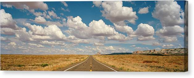 Scenics Canvas Print featuring the photograph Desert Road With Cloud Formations Above by Gary Yeowell