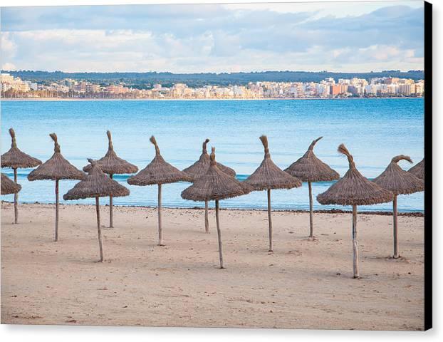 Straw Canvas Print featuring the photograph Straw Umbrellas On Empty Beach by Ingela Christina Rahm