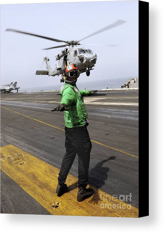 Uss Harry S Truman Canvas Print featuring the photograph Airman Checks The Takeoff Path by Stocktrek Images