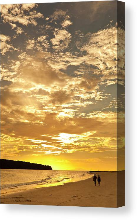 Scenics Canvas Print featuring the photograph Couple Walking On Beach At Sunset by Richard I'anson