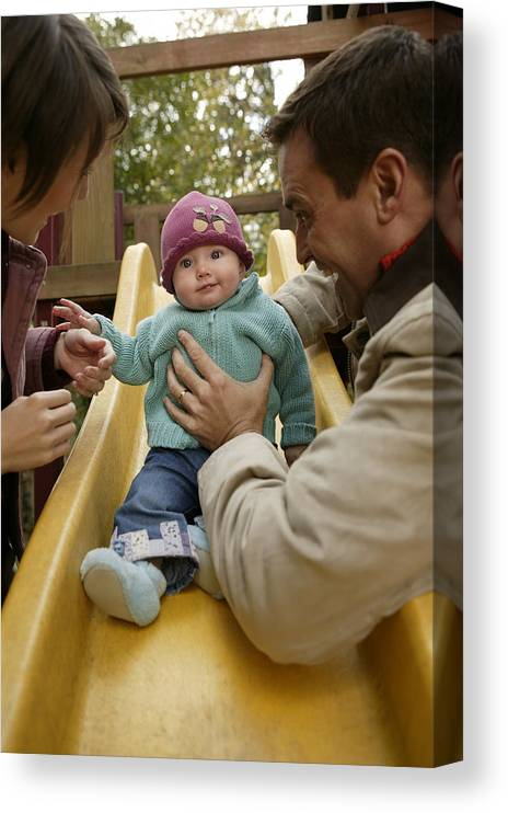 Mid Adult Women Canvas Print featuring the photograph Parents with baby playing on slide by Comstock Images