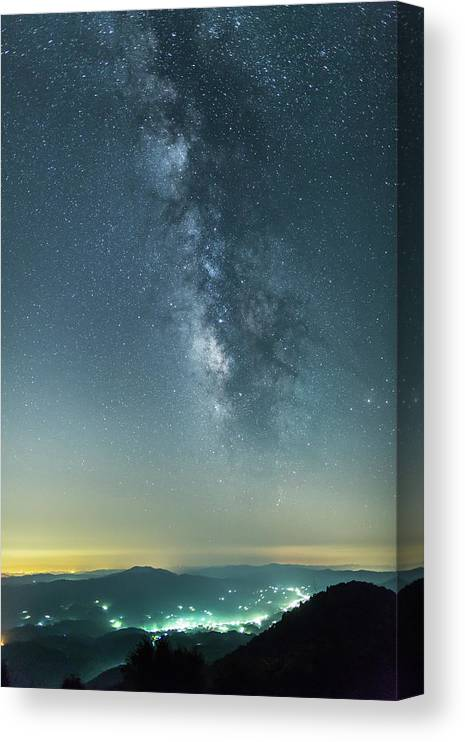 Scenics Canvas Print featuring the photograph The Milky Way Hovering Above A Town by Trevor Williams