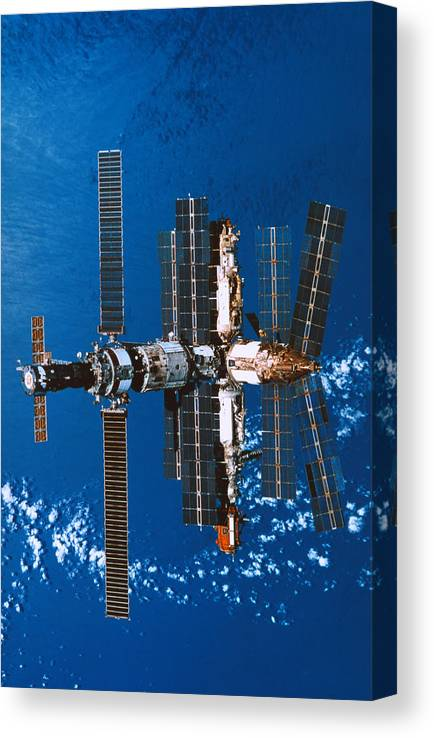 Vertical Canvas Print featuring the photograph A Space Station Orbiting In Space by Stockbyte