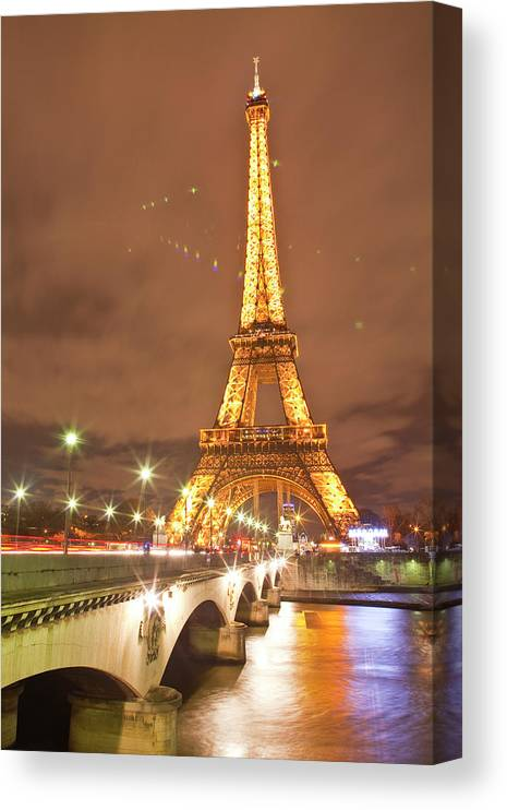 In A Row Canvas Print featuring the photograph The Eiffel Tower Lit Up At Night In by Julian Elliott Photography