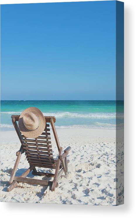 Scenics Canvas Print featuring the photograph Beach Chair With A Hat On An Empty Beach by Sasha Weleber