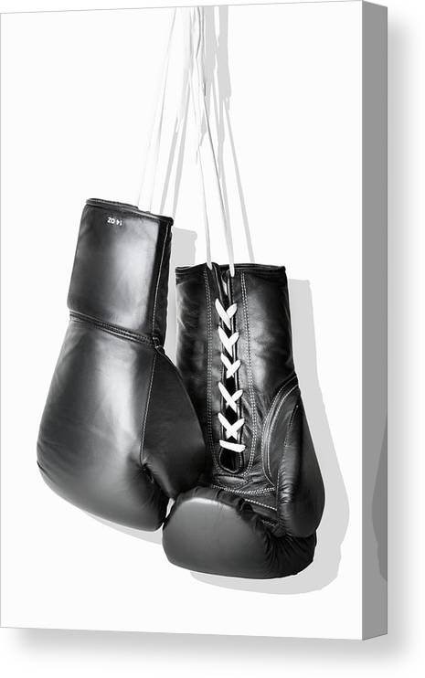 Hanging Canvas Print featuring the photograph Boxing Gloves Hanging Against White by Burazin