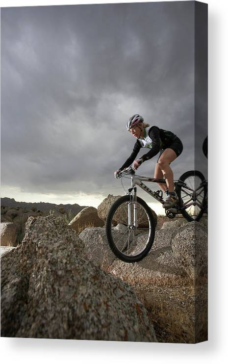 Sports Helmet Canvas Print featuring the photograph Female Rider Mountain Biking Between by Thomas Northcut