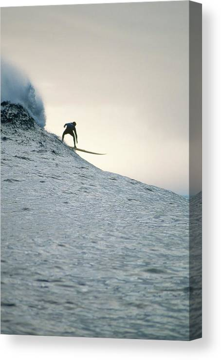 Scenics Canvas Print featuring the photograph Silhouette Of A Surfer Riding A Wave by Dominic Barnardt