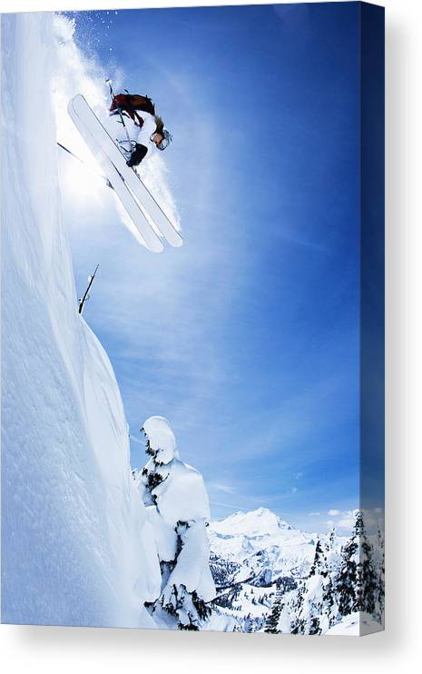 Ski Pole Canvas Print featuring the photograph Skier Jumping On Snowy Slope by Jakob Helbig