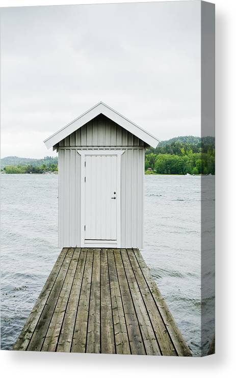 Sweden Canvas Print featuring the photograph A hut at the end of a wooden lake pier. by Roman Pretot