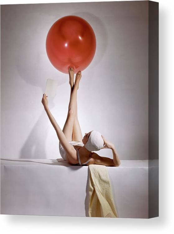 Fashion Canvas Print featuring the photograph A Model Balancing A Red Ball On Her Feet by Horst P Horst