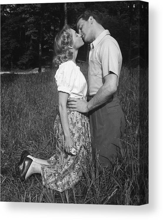 Heterosexual Couple Canvas Print featuring the photograph Couple Kissing Outdoors by George Marks