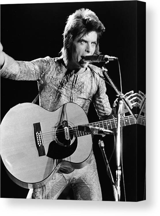 Ziggy Stardust - Persona Canvas Print featuring the photograph David Bowie Performing As Ziggy Stardust by Hulton Archive