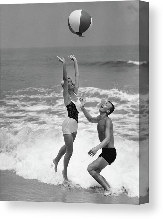 Young Men Canvas Print featuring the photograph Young Couple Playing With Beach Ball At by Stockbyte