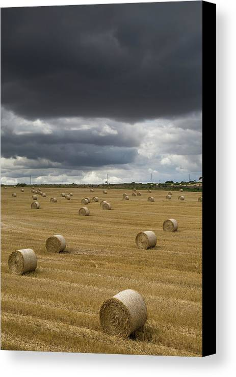 Cloud Canvas Print featuring the photograph Dark Storm Clouds Over A Field With Hay by John Short