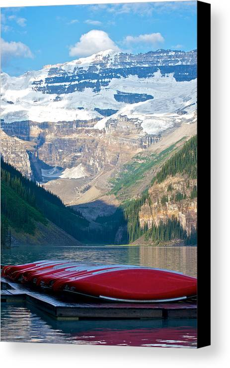 Alberta Canvas Print featuring the photograph Canoes On Lake Louise by Mike Horvath