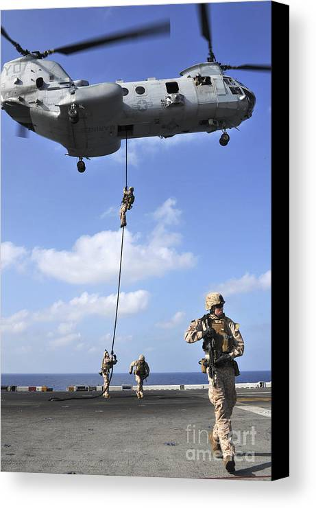 Warship Canvas Print featuring the photograph Marines Fast Rope From A Ch-46e Sea by Stocktrek Images