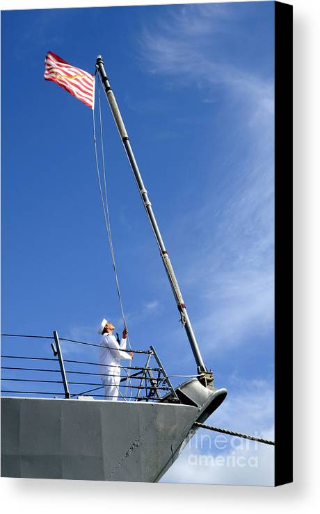 Pearl Harbor Canvas Print featuring the photograph A Sailor Lowers The U.s. Navy Jack by Stocktrek Images