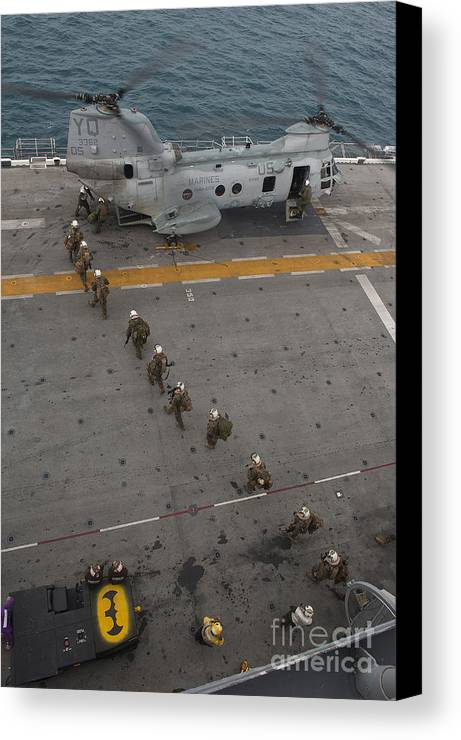 Flight Operations Canvas Print featuring the photograph Marines Embark A Ch-46e Sea Stallion by Stocktrek Images