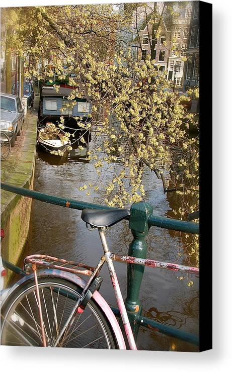 Bicycle Tree Canal Water Amsterdam Canvas Print featuring the photograph Bicycle In Amsterdam by Lucrecia Cuervo