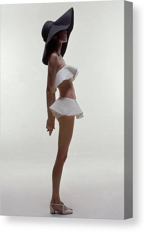 Fashion Canvas Print featuring the photograph A Model Wearing A Two Piece Bathing Suit by Bert Stern