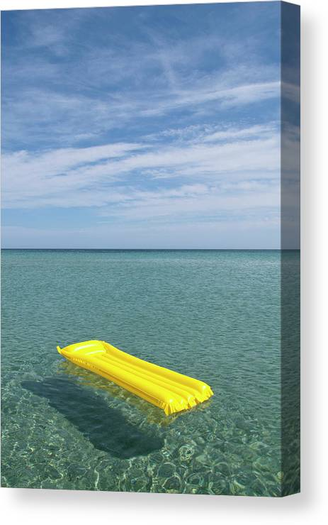 Tranquil Scene Canvas Print featuring the photograph A Yellow Inflatable Raft Floating On by Caspar Benson