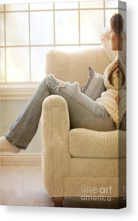 Woman; Lady; Female; Caucasian; Casual; Comfort; Comfortable; Lazy; Jeans; Socks; Sweater; Rips; Torn; Ripped; Hole; Chair; Sitting; Lounge; Lounging; Living Room; Indoors; Inside; Window; Wall; Carpet; Carpeting; Brunette; Crisp; Clean; Uncluttered; Sparse; Minimal; Alone; In Thought; Warm; Warmth Canvas Print featuring the photograph Relaxed by Margie Hurwich