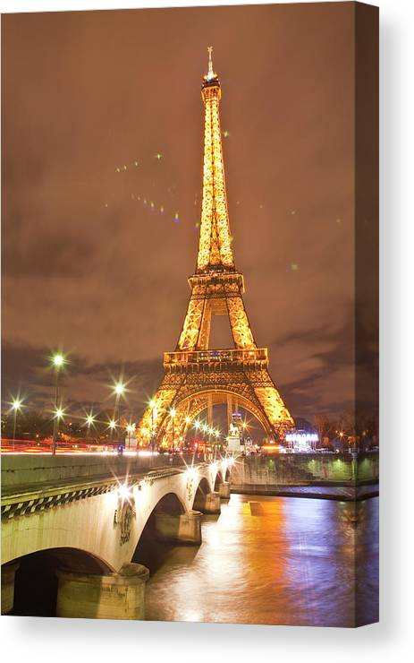 In A Row Canvas Print featuring the photograph The Eiffel Tower Lit Up At Night In 1 by Julian Elliott Photography