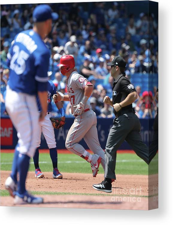 People Canvas Print featuring the photograph Mike Trout And Marco Estrada by Tom Szczerbowski
