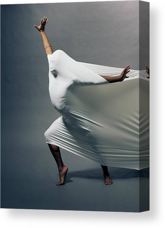 Hand Raised Canvas Print featuring the photograph Man Pressing Into Fabric, Arms Extended by Pm Images