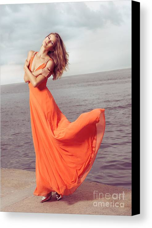 Woman Canvas Print featuring the photograph Young Woman In Orange Dress Flying In The Wind At Sea Shore by Oleksiy Maksymenko