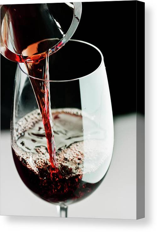 Alcohol Canvas Print featuring the photograph Red Wine Being Poured In A Glass by Juanmonino