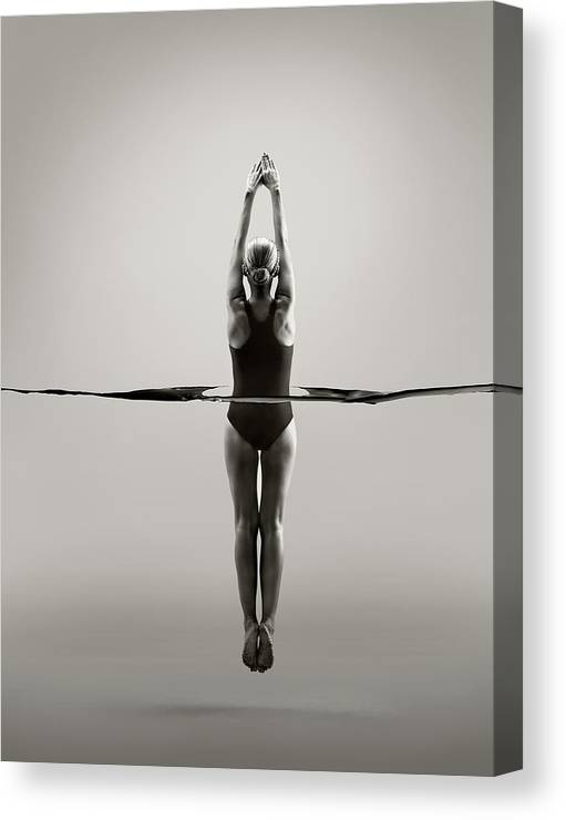 Diving Into Water Canvas Print featuring the photograph Rear View Of Female Swimmer by Jonathan Knowles