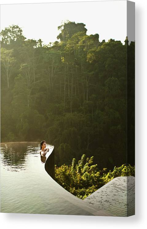 Tropical Rainforest Canvas Print featuring the photograph Woman In Infinity Pool At Sunrise. Bali by Matthew Wakem