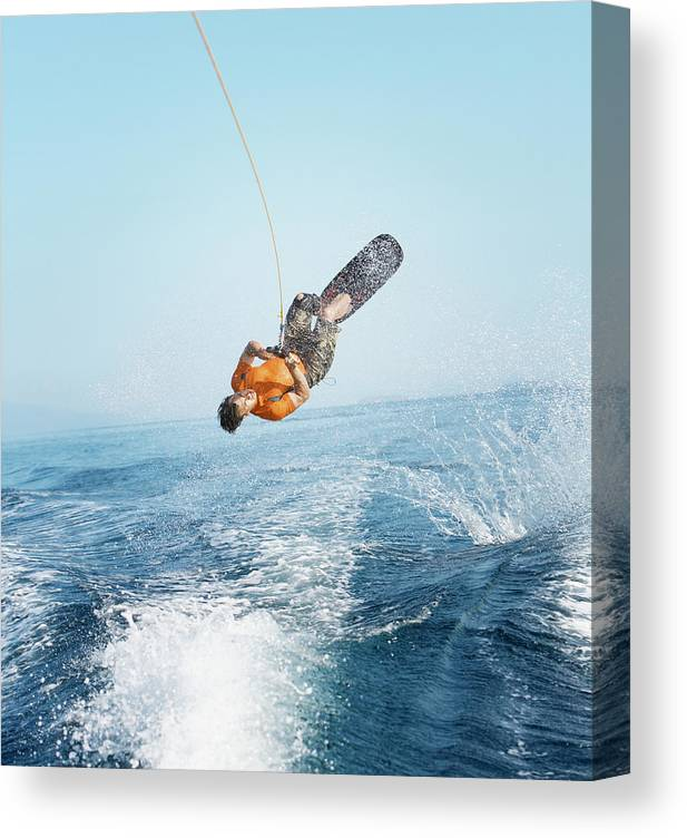 One Man Only Canvas Print featuring the photograph Man Performing Wakeboarding Stunt At Sea by Paul Bradbury