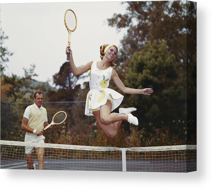 Heterosexual Couple Canvas Print featuring the photograph Couple On Tennis Court, Woman Jumping by Tom Kelley Archive