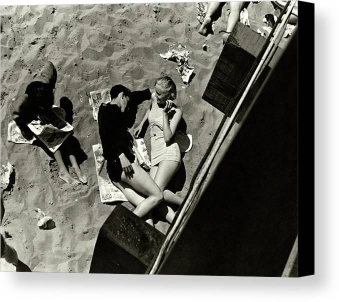 Swimwear Canvas Print featuring the photograph A Young Couple Lying On A Beach by Lusha Nelson