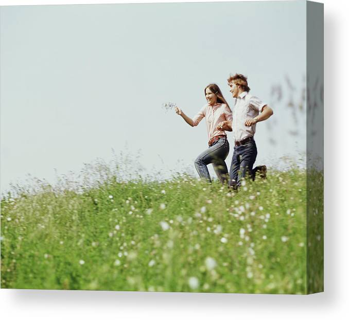 Photography Canvas Print featuring the photograph 1970s Boy Girl Running Field by Vintage Images