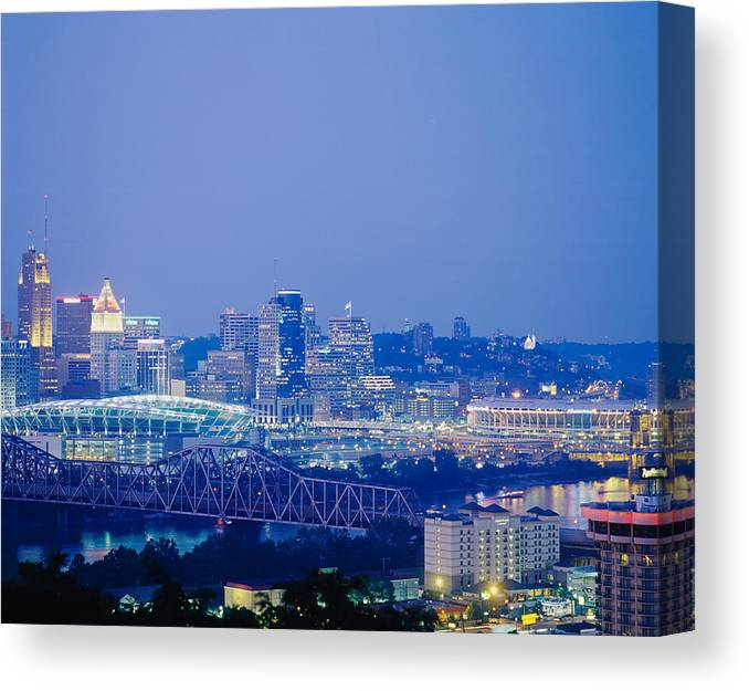 Photography Canvas Print featuring the photograph Buildings In A City Lit Up At Dusk by Panoramic Images