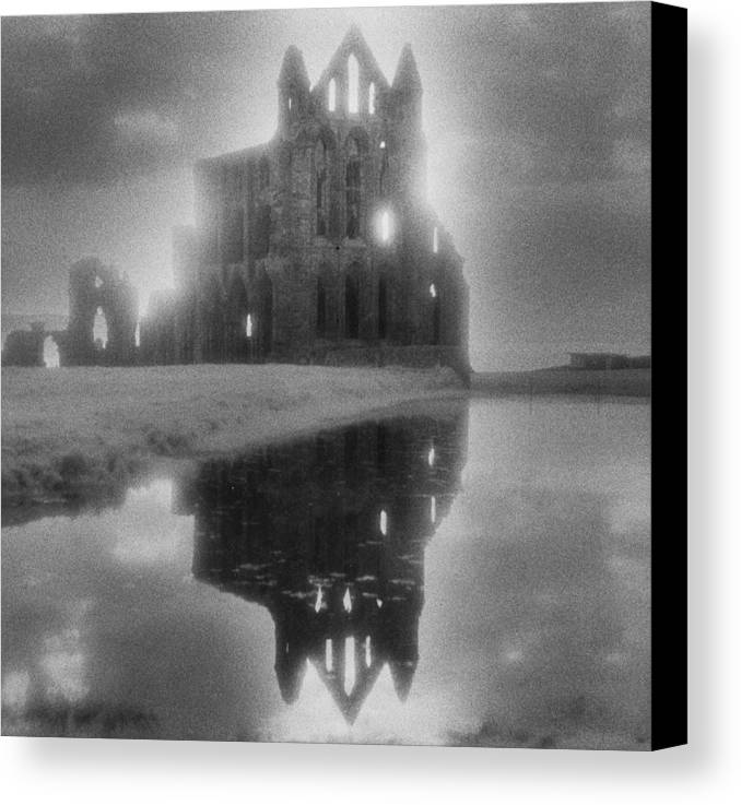 Eerie; Atmospheric; Spooky; Haunted; Haunting; Dramatic; Striking; Misty; Hazy; Lake; Reflection; English; Architecture; Exterior; Ruin; Ruins Canvas Print featuring the photograph Whitby Abbey by Simon Marsden