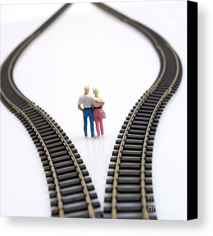 Unfocused Canvas Print featuring the photograph Couple Two Figurines Between Two Tracks Leading Into Different Directions Symbolic Image For Making Decisions by Bernard Jaubert