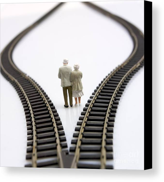Contemplates Canvas Print featuring the photograph Figurines Between Two Tracks Leading Into Different Directions Symbolic Image For Making Decisions. by Bernard Jaubert