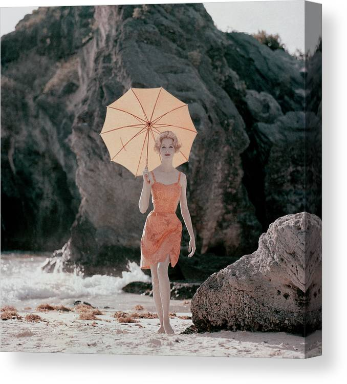 Model Walking With Peach Colored Umbrella Canvas Print featuring the photograph Vogue January 1st, 1959 by Jerry Schatzberg