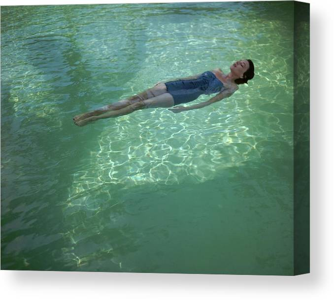 Exterior Canvas Print featuring the photograph A Model Floating In A Swimming Pool by John Rawlings