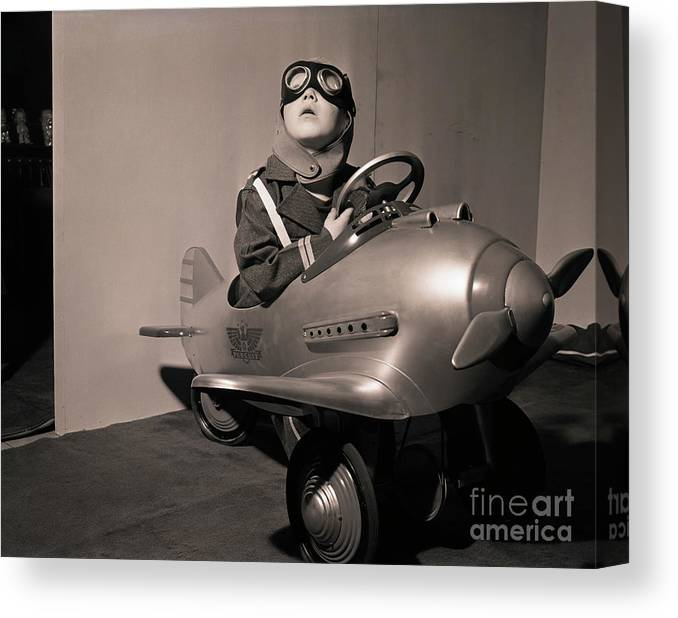Child Canvas Print featuring the photograph Boy In Aviator Suit Sitting In Toy Plane by Bettmann