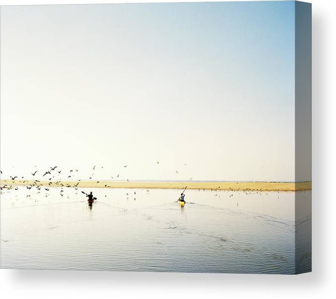 People Canvas Print featuring the photograph Men Paddling Kayaks To The Beach by Julien Capmeil