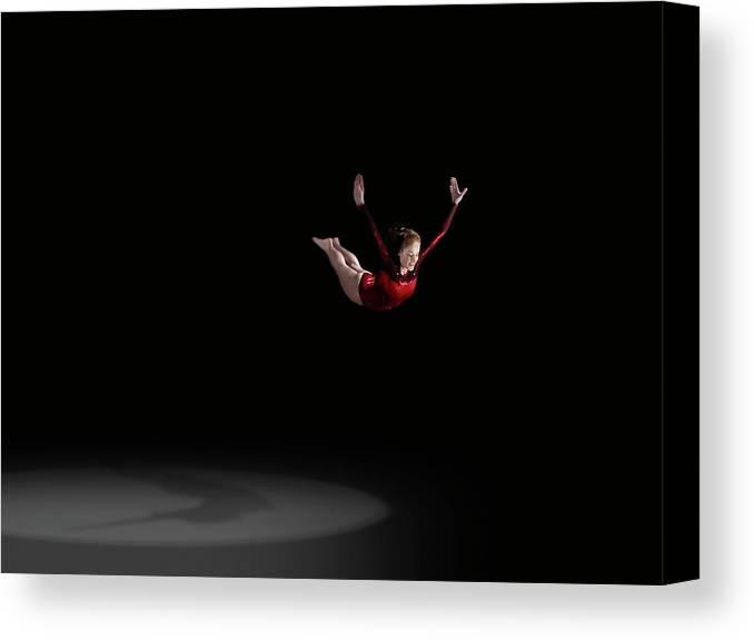 Focus Canvas Print featuring the photograph Female Gymnast Soaring Through Air by Mike Harrington
