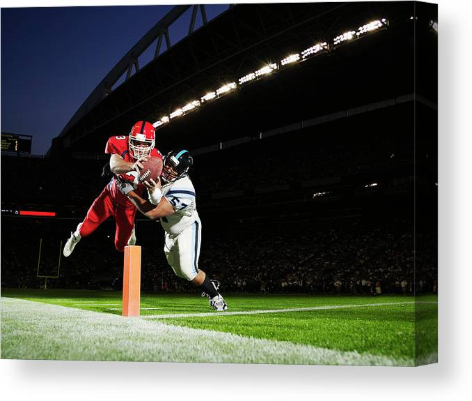 Sports Helmet Canvas Print featuring the photograph Football Player Diving Into End Zone by Thomas Barwick